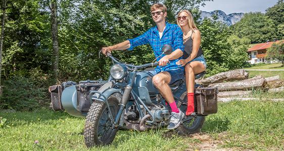 Stefan und Lena sitzen auf einem alten Motorrad mit Beiwagen und tragen bunte Socken von der Marke gigando Premium in den Farben rot und rosa